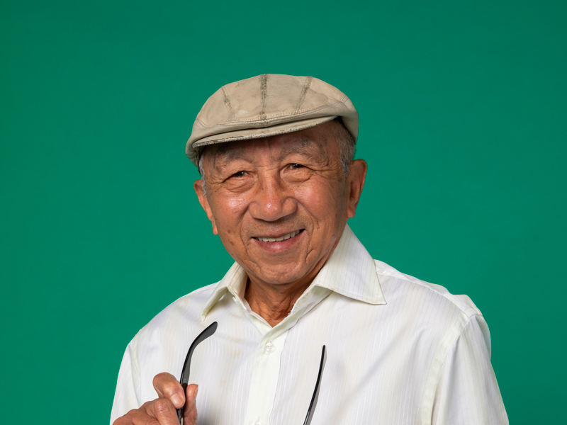 Image of an older man wearing a beret and holding his glasses by the arm.