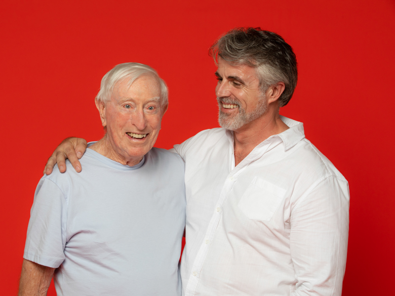 Image of two men looking like father and son with their arms around each other. The son is smiling and looking at this father.