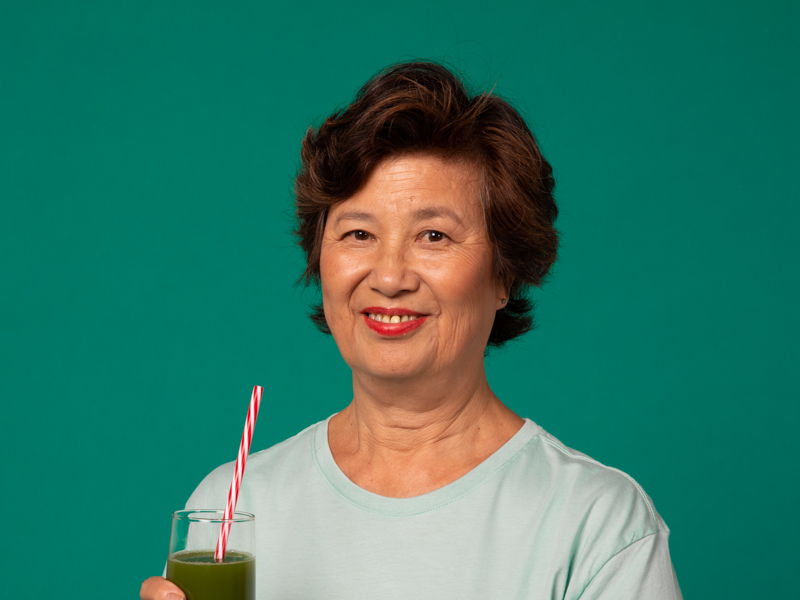 Image of an asian lady with a green smoothie