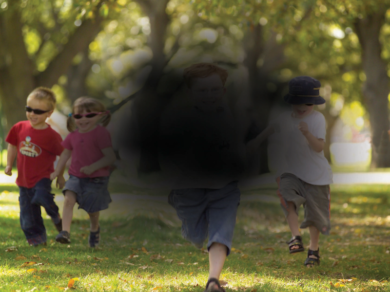 Image shows a group of children running. Black spot covers centre of image, to simulate loss of vision from age-related macular degeneration.