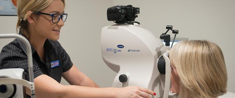 Image shows an optometrist performing an OCT scan on a patient.