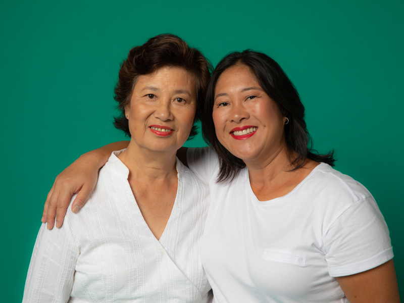 Image of an Asian mother and daughter with their arms around each other, smiling at the camera