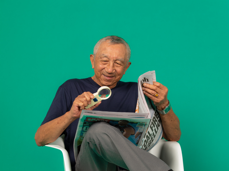 Image of a senior man reading a newspaper with a magnifier