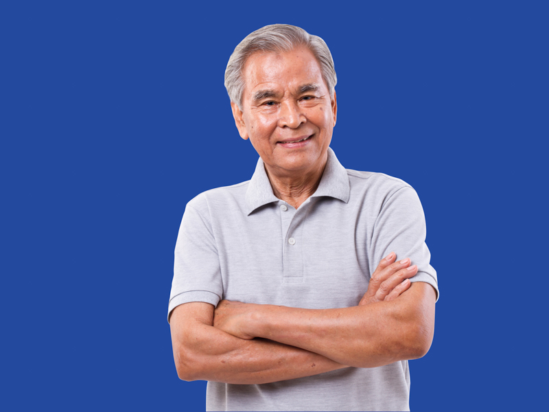 Image of an older Asian man in a blue golf shirt smiling at the camera