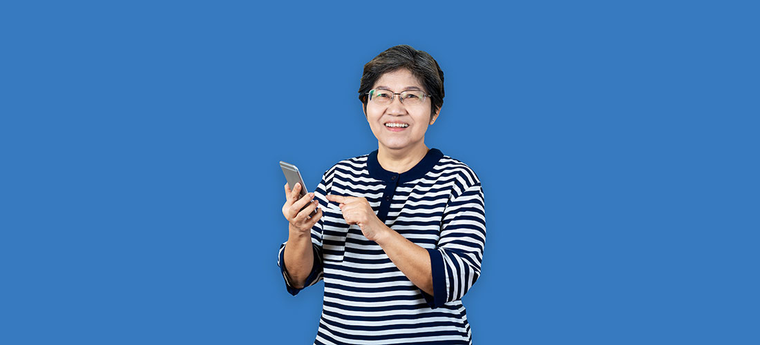 Asian lady with a mobile phone on a blue background
