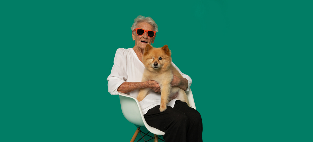 Image of a lady with sunglasses and her dog on her lap.