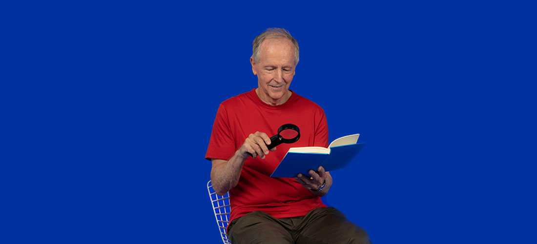 Image of a senior man reading a book with a magnifier
