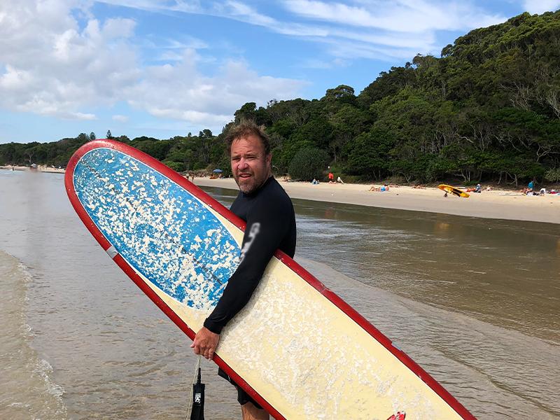 Image shows Shane Dunbar-Reid with his surfboard.